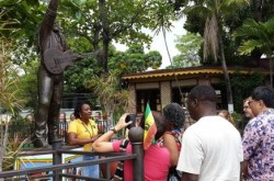 REGGAE ICON Bob Marley's music was one of the areas of exposure during the immersion experience of the participants in the Liturgical music workshop in Jamaica recently.  Here tour guide at the Bob Marley music shares the story of this reggae icon at the foot of his statue.